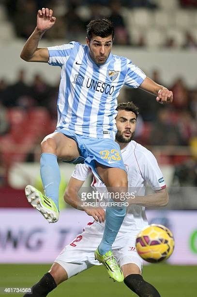 Malaga's defender Miguel Torres vies with Sevilla's midfielder Vicente Iborra during the Spanish league football match Sevilla FC vs Malaga CF at the...