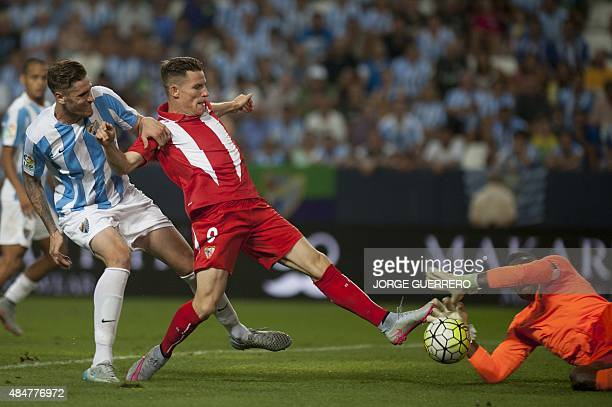 Malaga's defender Raul Albentosa and Malaga's Cameroonian goalkeeper Carlos Kameni vies with Sevilla's French forward Kevin Gameiro during the...