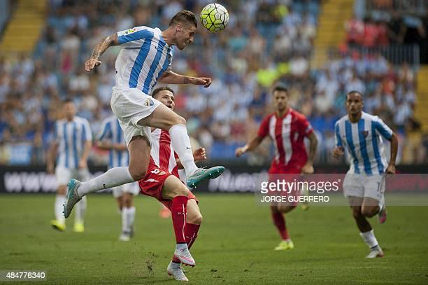 Malaga's defender Raul Albentosa vies with Sevilla's French forward Kevin Gameiro during the Spanish league football match Malaga CF vs Sevilla FC at...