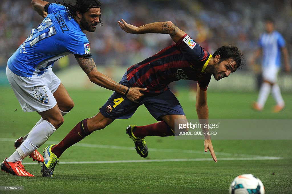 Malaga's defender Sergio Sanchez (L) vies for the ball with Barcelona's midfielder Cesc Fabregas during the Spanish league football match Malaga CF vs FC Barcelona at Rosaleda stadium in Malaga on August 25, 2013. Barcelona won 1-0. AFP PHOTO/ JORGE GUERRERO