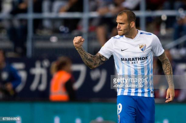 Malaga's forward Sandro Ramirez celebrates after scoring during the Spanish league football match Malaga CF vs Sevilla FC at La Rosaleda stadium in...