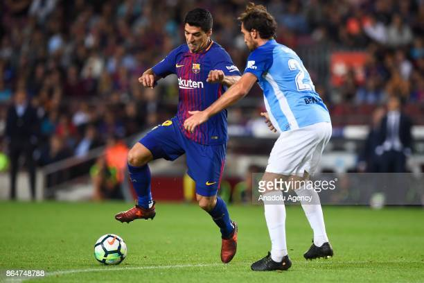 Malaga's French defender Paul Baysse vies with Barcelona's Uruguayan forward Luis Suarez during the Spanish league football match FC Barcelona vs...