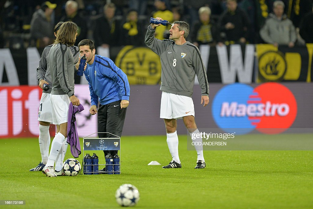 Malaga's French midfielder Jeremy Toulalan (R) puts water on his face before the UEFA Champions League quarter-final second-leg football match Borussia Dortmund vs Malaga CF in Dortmund, western Germany on April 9, 2013. ANDERSEN