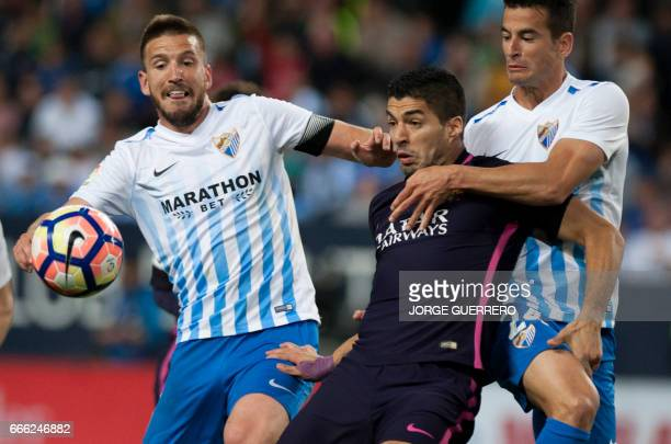 Malaga's midfielder Ignacio Camacho and defender Luis Hernandez vie with Barcelona's Uruguayan forward Luis Alberto Suarez during the Spanish league...