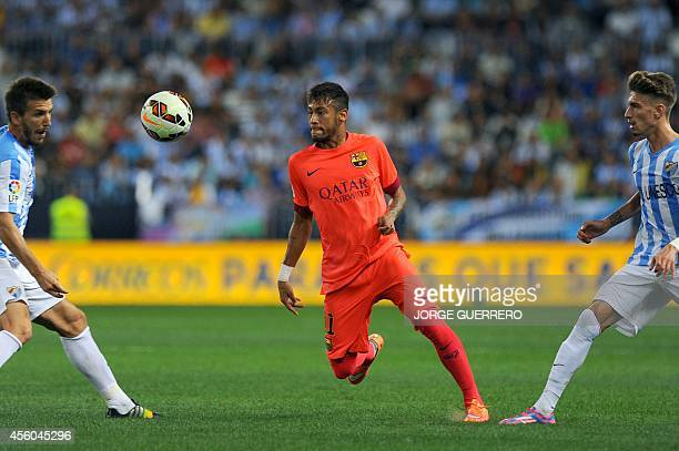 Malaga's midfielder Ignacio Camacho and forward Samuel Castillejo vies with Barcelona's Brazilian forward Neymar da Silva Junior during the Spanish...