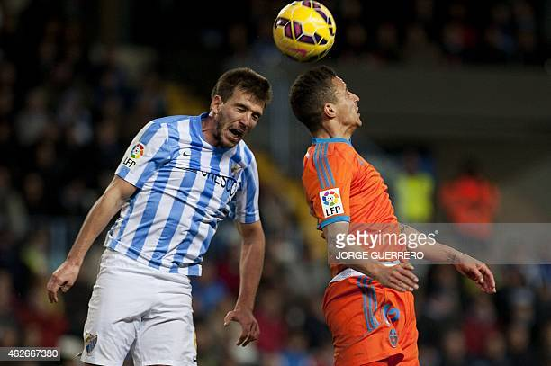 Malaga's midfielder Ignacio Camacho vies with Valencia's Brazilian forward Rodrigo Moreno during the Spanish league football match Malaga CF vs...