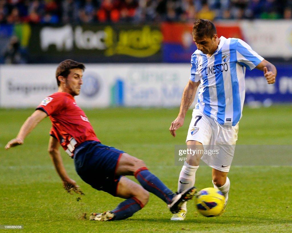 Malaga's midfielder Joaquin Sanchez (R) vies with Osasuna's midfielder Oier Sanjurjo (L) during the Spanish league football match CA Osasuna vs Malaga CF on November 17, 2012 at the Reyno de Navarra stadium in Pamplona.