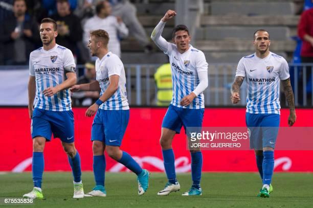 Malaga's midfielder Pablo Fornals celebrates past teammates after scoring during the Spanish league football match Malaga CF vs Sevilla FC at La...