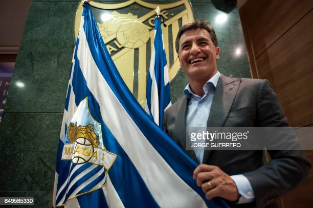 Malaga's new coach Jose Miguel Gonzalez Martin del Campo aka Michel smiles as he poses with Malaga CF flag during his official presentation at the...