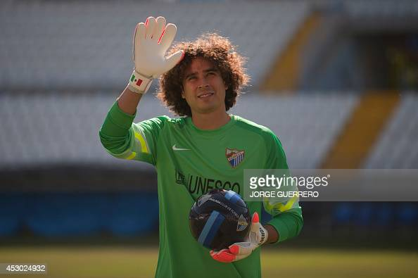 Malaga's new Mexican goalkeeper Guillermo Ochoa waves to supporters during his official presentation at the Rosaleda stadium in Malaga on August 1...