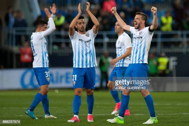 Malaga's players celebrates after winning 20 the Spanish league football match Malaga CF vs FC Barcelona at La Rosaleda stadium in Malaga on April 8...