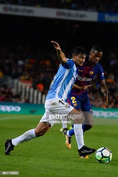 Malaga's Uruguayan midfielder Gonzalo Castro vies with Barcelona's Portuguese defender Nelson Semedo during the Spanish league football match FC...