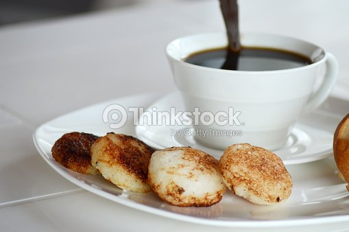 Malagasy donuts from Madagascar with coffee: mofogasy (malagasy sweet donuts) and ramanonaka (malagasy salty donuts) and cutted French bread.
