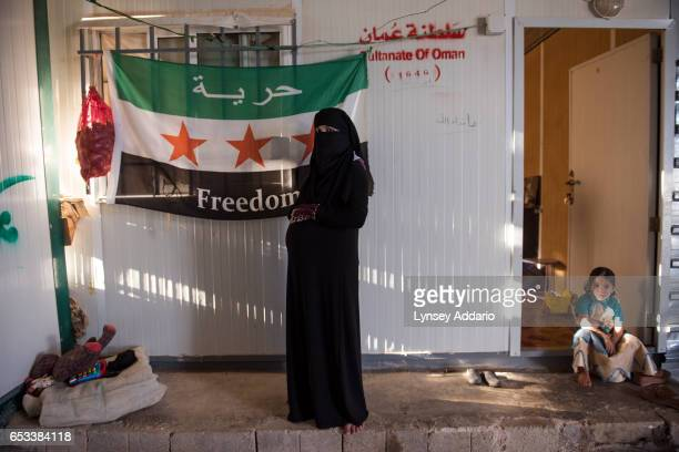 Malak Rifai a Syrian refugee from Daraa poses for a portrait at nine months pregnant in front of a Syrian flag in her family's trailer in the Zaatari...