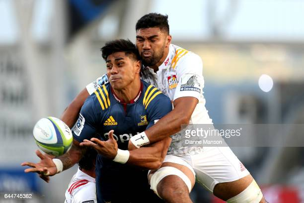 Malakai Fekitoa of the Highlanders passes the ball in the tackle of Taleni Seu of the Chiefs during the round one Super Rugby match between the...