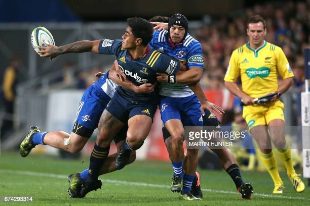 Malakai Fekitoa of the Otago Highlanders get his pass away in a tackle during the Super Rugby match between the Otago Highlanders of New Zealand and...