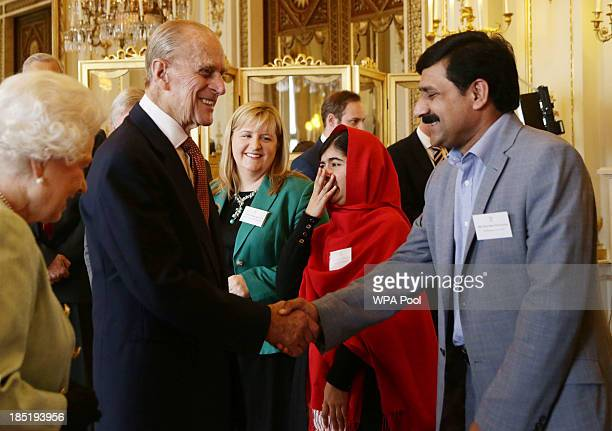 Malala Yousafzai reacts to a comment made by the Philip Duke of Edinburgh as he greets her father Ziauddin during a Reception for Youth Education and...
