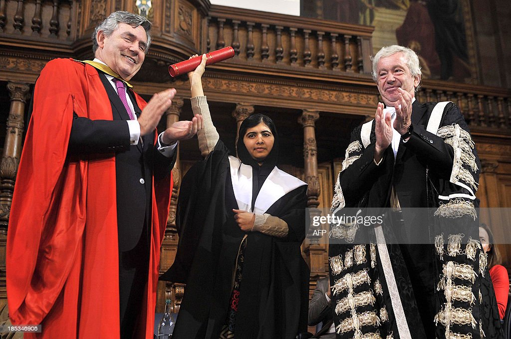Malala Yousafzai (C), the Pakistani girl shot by the Taliban after campaigning for girls' education, stands between British former prime minister Gordon Brown (L) and university Principal Professor Timothy O'Shea as she receives an honorary masters degree from the University of Edinburgh during the first Global Citizenship Commission meeting at the university in Scotland on October 19, 2013. AFP PHOTO/ANDY BUCHANAN