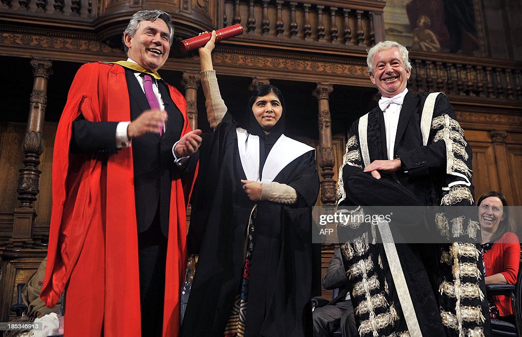 Malala Yousafzai (C), the Pakistani girl shot by the Taliban after campaigning for girls' education, stands between British former prime minister Gordon Brown (L) and university Principal Professor Timothy O'Shea as she receives an honorary masters degree from the University of Edinburgh during the first Global Citizenship Commission meeting at the university in Scotland on October 19, 2013.