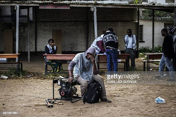 A Malawian Electoral Commission officer sits on a generator as polling was delayed by several hours at a voting station in Blantyre central district...