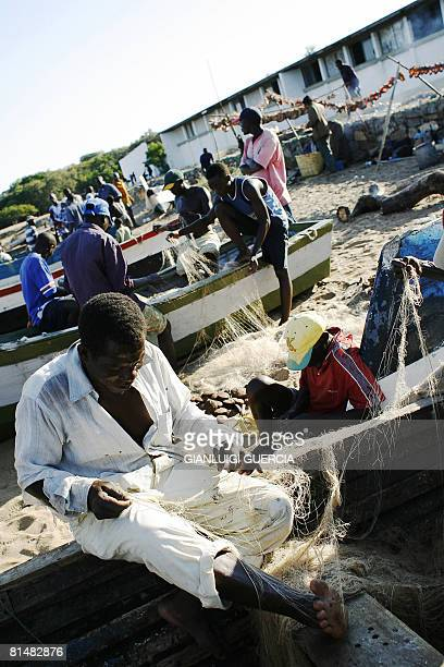Malawian fishermen fix and wrap their fishing nets on May 14 2008 on the beach of Lake Malawi in Senga bay Salima central Malawi Home to more than...