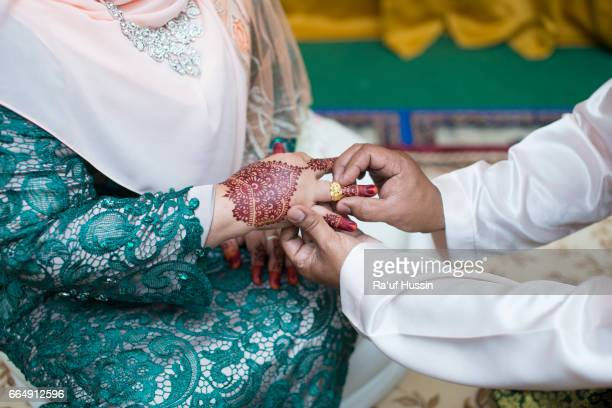 Malay wedding couple putting a ring to the bride