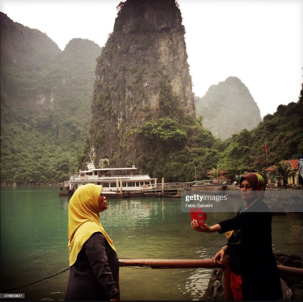 Malay women take pictures with their tablet in Ha Long Bay, Vietnam