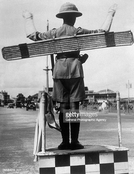 A Malayan traffic policeman with a semaphore board on his back