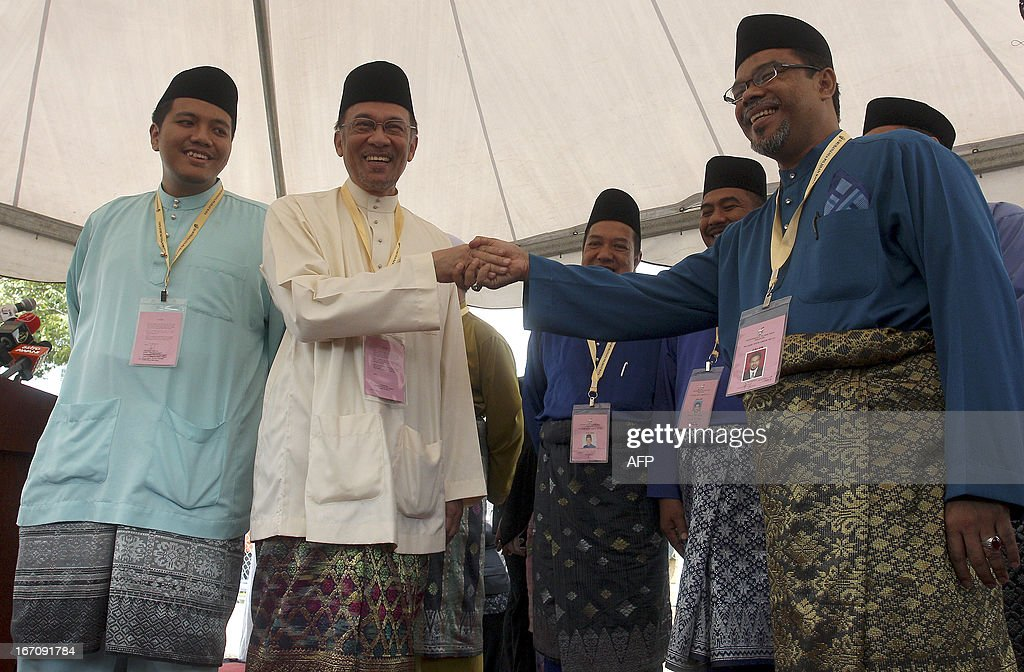 Malaysia opposition leader Anwar Ibrahim (2nd L) and Malaysia's ruling National Front coalition, or Barisan Nasional candidate Mazlan Ismail (R) shake hands after submitting their election nominations in Permatang Pauh on April 20, 2013. Malaysian premier Najib Razak and opposition leader Anwar Ibrahim on Saturday kicked off their campaigns for May 5 elections likely to be the country's closest ever. AFP PHOTO / MOHD RASFAN