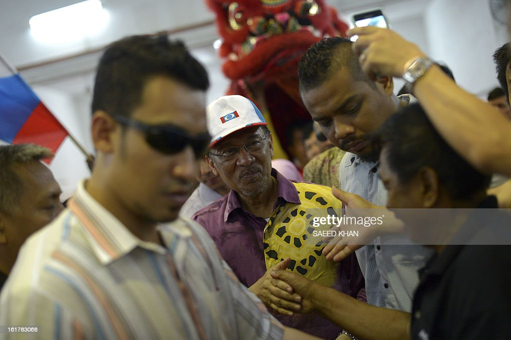 Malaysia opposition leader Anwar Ibrahim shakes hand with his supporters as he arrives to address a corner meeting in the outskirts of Kuala Lumpur on February 16, 2013. Anwar condemned the detention of Australian senator Nick Xenophon 'in the strongest terms', saying allegations that he was a security threat were 'completely without foundation'. Xenophon and the other politicians were to meet members of electoral reform group Bersih, which has organised last year's rally, and others including opposition leader Anwar Ibrahim and Election Commission officials .AFP PHOTO / Saeed KHAN