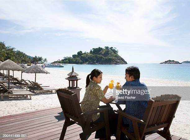 Malaysia, Redang Island, man and woman drinking cocktails on beach