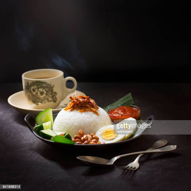 Malaysia traditional food 'Nasi lemak' and a cup of coffee on rustic moody table top.