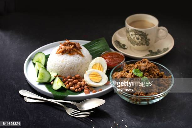 Malaysia traditional food 'Nasi lemak' served with 'Rendang' and milk coffee.