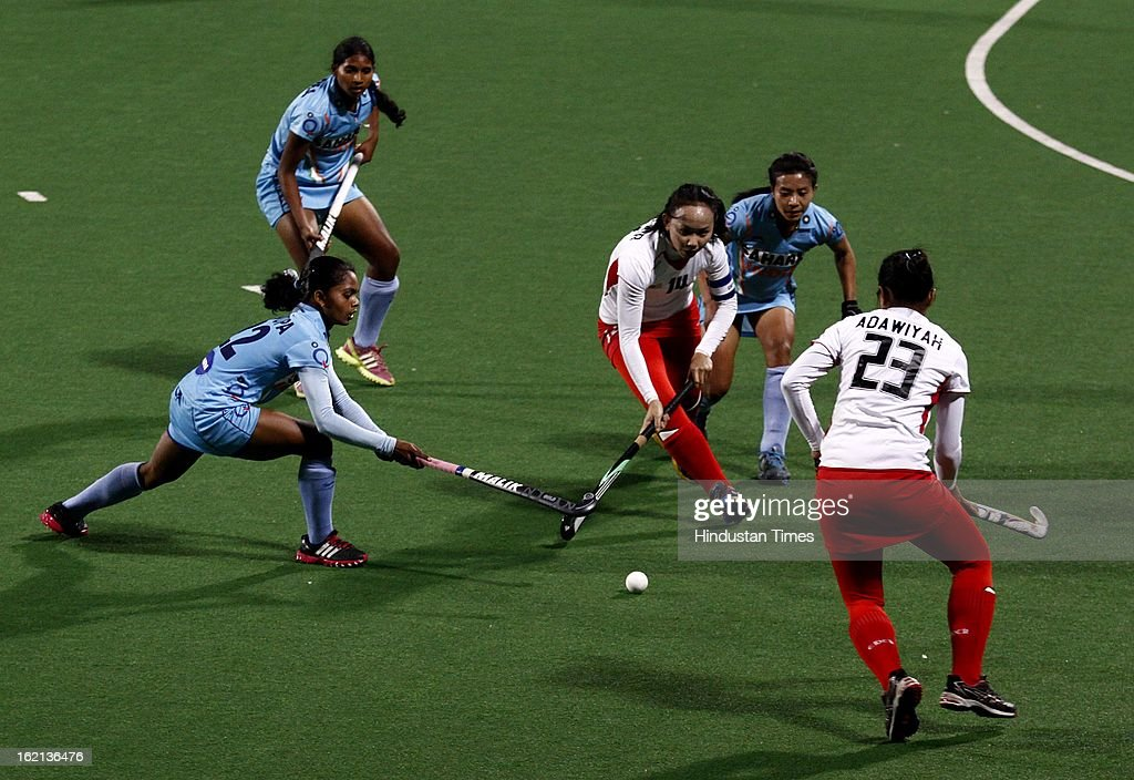 Malaysia Women Hockey Player Nadia Rahman tackled by the Indian women hockey players during the Hockey World League Round 2 match at Dhyan Chand Stadium on February 19, 2013 in New Delhi, India. Indian Eves won the match 3-0.