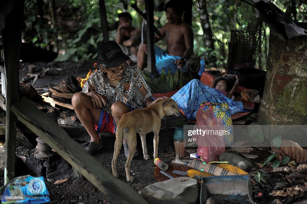 MalaysiaenvironmentculturePenanFEATURE by Dan Martin This picture taken on November 17 2013 shows a family of the Penan tribe sitting inside a garage...