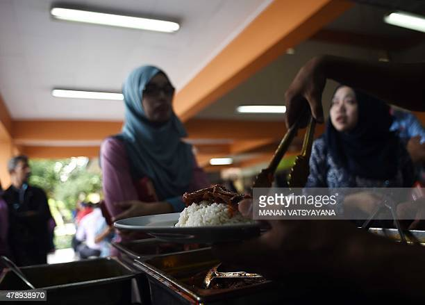 Malaysiafoodlifestylecuisine FEATURE by Satish Cheney In this picture taken March 25 2015 a Malaysian stall assistant serves Nasi Lemak dish on a...