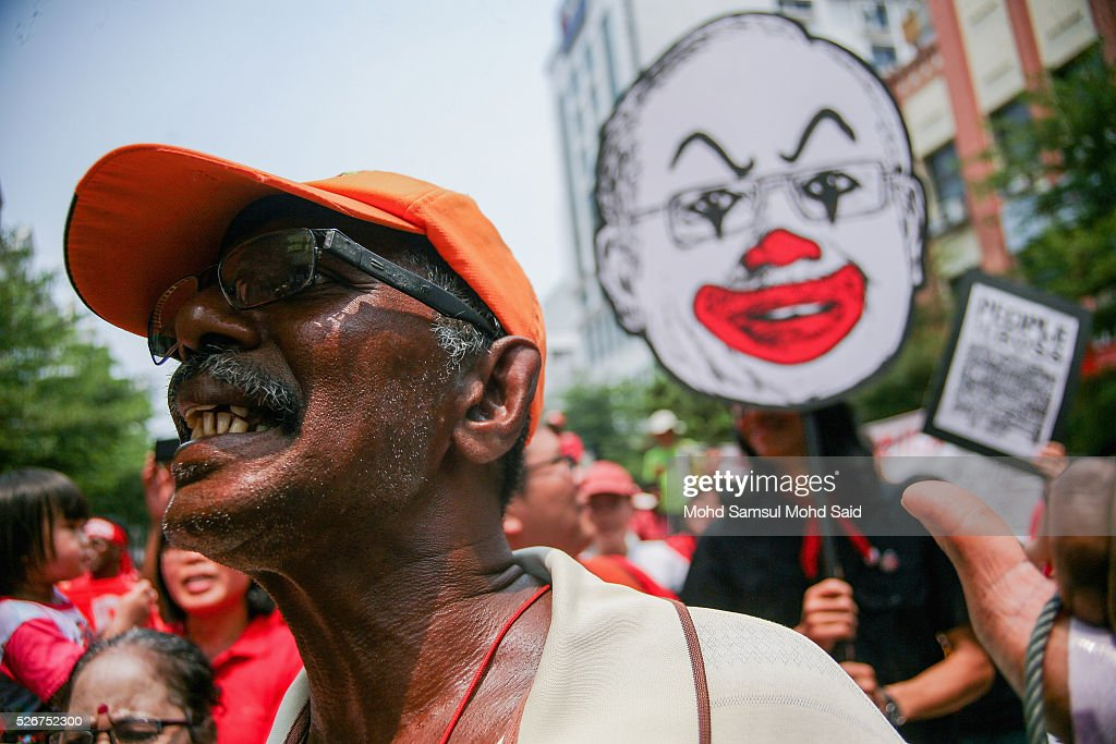 Malaysian activist shout to demand a higher minimum wage as a Prime Minister Najib Razak clown poster in behind during May Day Protest near shopping mall on May 1, 2016 in Kuala Lumpur, Malaysia. More than 70 NGOs and activist groups forming part of the Mayday were focusing on 'ordinary people' issues according to organizer. The May Day rally is focused on fighting for the rights of workers including a higher minimum wage of MYR1,500 (USD 389.00) amid the current economic situation in Malaysia and political issues like 1Malaysia Development Berhad (1MDB) and demanding the resignation of Prime Minister Najib Razak.