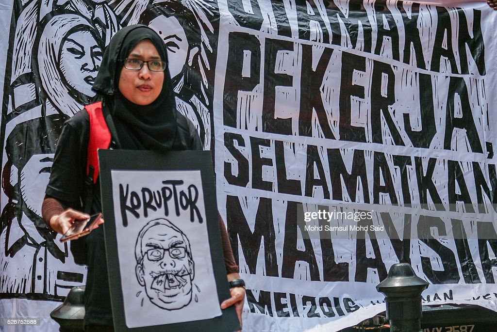 Malaysian activist show a placard message during May Day Protest near shopping mall on May 1, 2016 in Kuala Lumpur, Malaysia. More than 70 NGOs and activist groups forming part of the Mayday were focusing on 'ordinary people' issues according to organizer. The May Day rally is focused on fighting for the rights of workers including a higher minimum wage of MYR1,500 (USD 389.00) amid the current economic situation in Malaysia and political issues like 1Malaysia Development Berhad (1MDB) and demanding the resignation of Prime Minister Najib Razak.