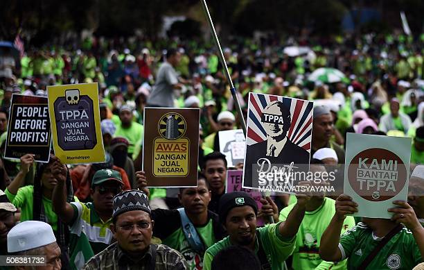 Malaysian activists hold placards denouncing the USled TransPacific Partnership Agreement during a protest in Kuala Lumpur on January 23...