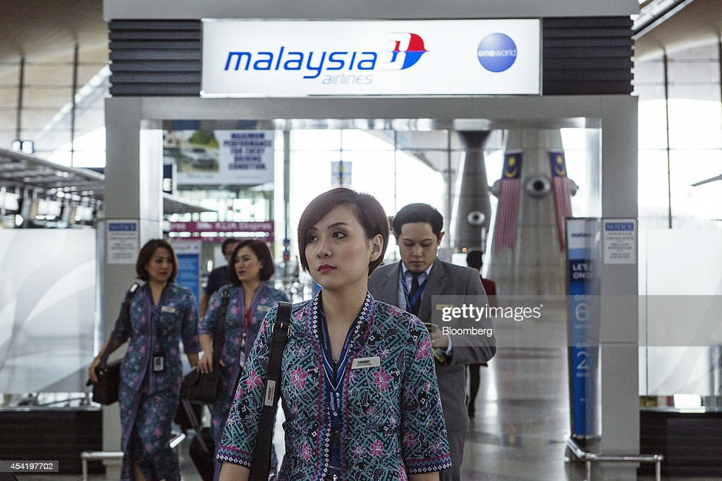 Malaysian Airline System Bhd. (MAS) air crew walk through Kuala Lumpur International Airport (KLIA) in Sepang, Malaysia, on Tuesday, Aug. 26, 2014. Malaysia Airlines are scheduled to release second quarter earnings Aug. 27 as the airline considers job cuts, a review of aircraft orders and replacing its chief executive officer after the national carrier suffered two disasters this year, people familiar with the plan said. Photographer: Charles Pertwee/Bloomberg via Getty Images