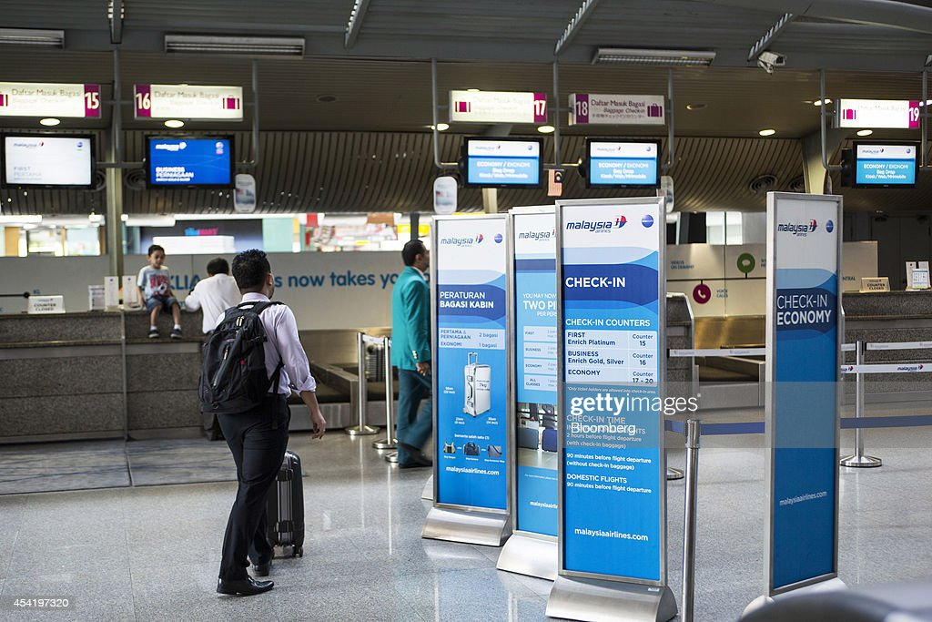 Malaysian Airline System Bhd. (MAS) signage is displayed as a passenger arrives to check in at the KLIA Ekspres counter at Kuala Lumpur Sentral station in Kuala Lumpur, Malaysia, on Tuesday, Aug. 26, 2014. Malaysia Airlines are scheduled to release second quarter earnings Aug. 27 as the airline considers job cuts, a review of aircraft orders and replacing its chief executive officer after the national carrier suffered two disasters this year, people familiar with the plan said. Photographer: Charles Pertwee/Bloomberg via Getty Images
