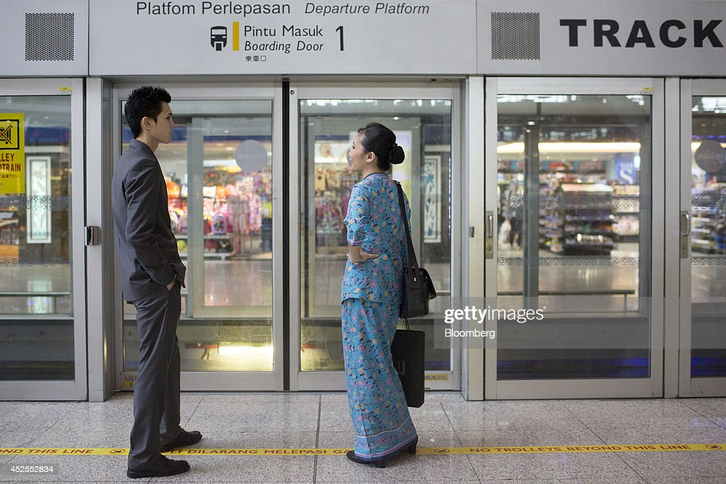 A Malaysian Airline Systems Bhd. (MAS) flight attendant, right, stands at a train platform at Kuala Lumpur International Airport (KLIA) in Sepang, Malaysia, on Tuesday, July 22, 2014. Malaysian Air, reeling from its second disaster in four months, plans to present a revival plan to its state-run parent Khazanah Nasional Bhd. this week, people familiar with the matter said, amid reports the national carrier is likely near the end of its days as a publicly traded company. Photographer: Brent Lewin/Bloomberg via Getty Images