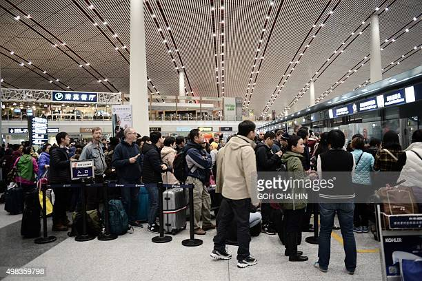 Malaysian airlines' passengers wait for their flights at the Beijing Capital International airport after heavy snowstorm cancelled and delayed...