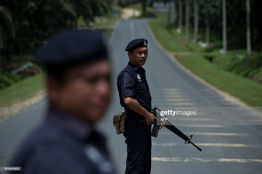 Malaysian armed policemen man a security check in Sahabat 7 on the road leading to Tanjung Tanduo, in the areas where suspected Philippine militants are holding off, on the Malaysian island of Borneo on February 18, 2013. Followers of a Philippine sultan who crossed to the Malaysian state of Sabah this month will not leave and are reclaiming the area as their ancestral territory, the sultan said on February 17 amid a tense standoff. AFP PHOTO / MOHD RASFAN