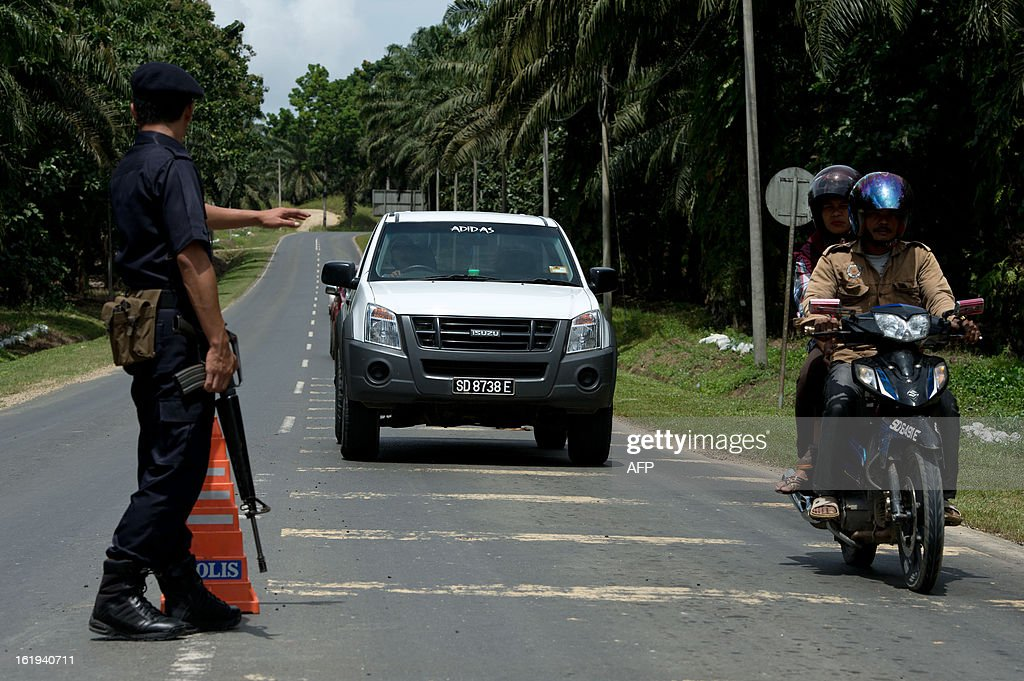 A Malaysian armed policemen (L) mans a security check in Sahabat 7 on the road leading to Tanjung Tanduo, in the areas where suspected Philippine militants are holding off, on the Malaysian island of Borneo on February 18, 2013. Followers of a Philippine sultan who crossed to the Malaysian state of Sabah this month will not leave and are reclaiming the area as their ancestral territory, the sultan said on February 17 amid a tense standoff.