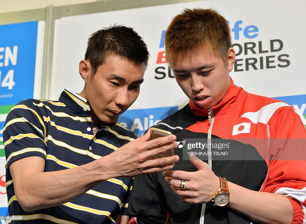 Malaysian badminton star Lee Chong Wei (L) and Japanese rival Kenichi Tago (R) check a smartphone after a press conference for the Japan open badminton tournament in Tokyo on June 10, 2014. Japan Open badminton tournament will start from June 11 through 15. AFP PHOTO / Yoshikazu TSUNO