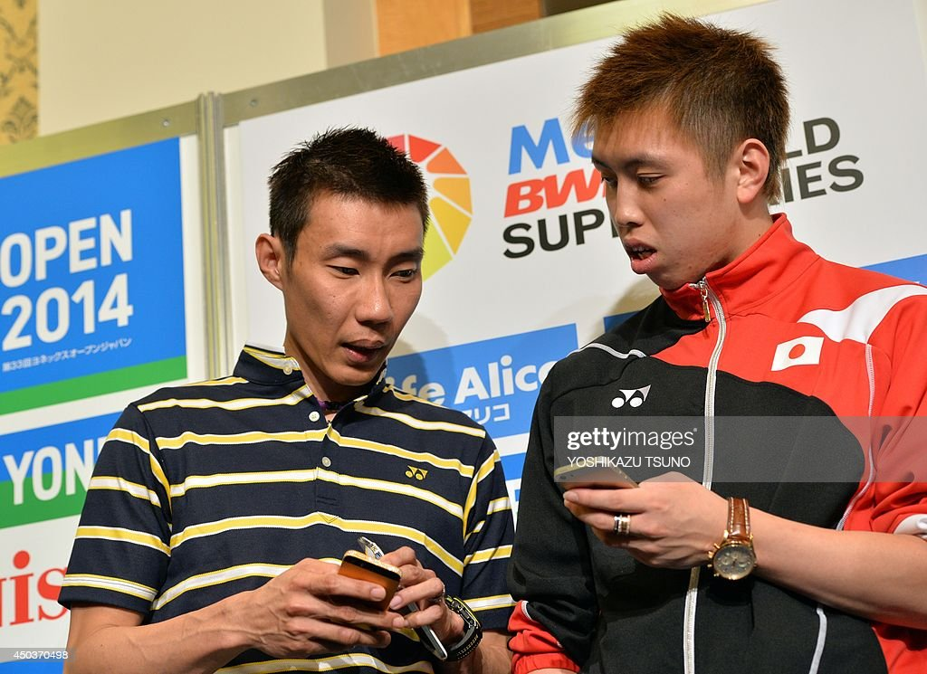 Malaysian badminton star Lee Chong Wei (L) and Japanese rival Kenichi Tago (R) check their smartphones after a press conference for the Japan open badminton tournament in Tokyo on June 10, 2014. Japan Open badminton tournament will start from June 11 through 15. AFP PHOTO / Yoshikazu TSUNO