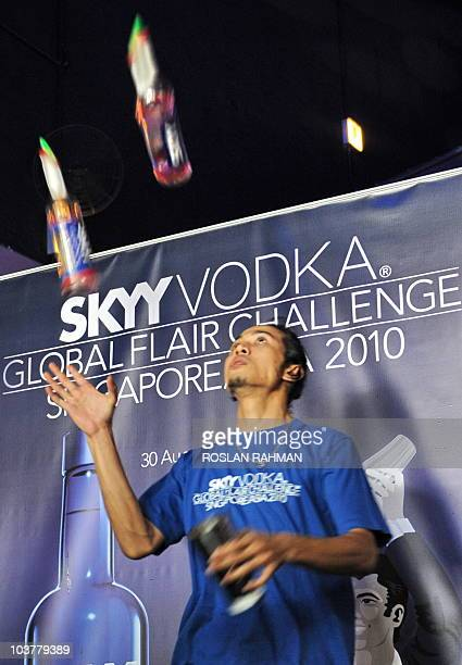 Malaysian bartender Mohomed Ishfahan exhibits his skill by juggling bottles of vodka during a regional flair bartending competition at the Skyy Vodka...