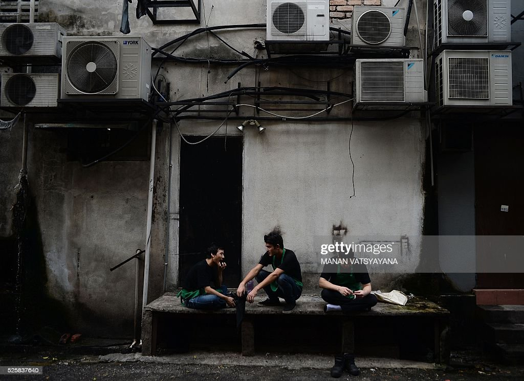 Malaysian chefs and servers take a break in the back alley of a restaurant in Kuala Lumpur on April 29, 2016. / AFP / MANAN
