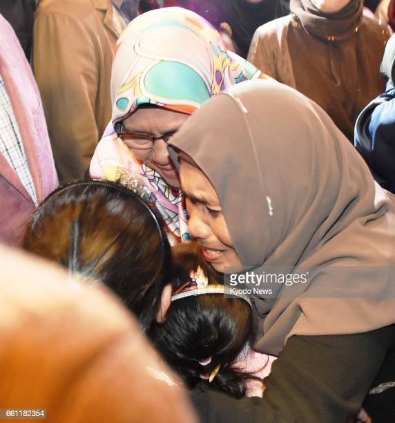 Malaysian children are hugged by family members after arriving at Kuala Lumpur International Airport on March 31 2017 Nine Malaysian nationals who...